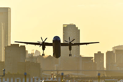 Airliner flying over London skyscrapers - p1048m2024246 by Mark Wagner