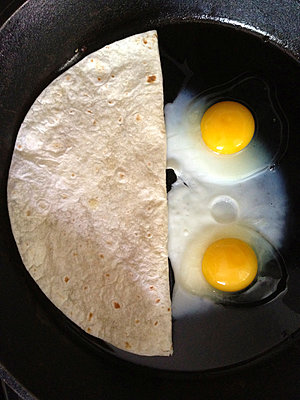 Overhead view of flatbread and fried eggs in pan - p1166m1152081 by Cavan Images