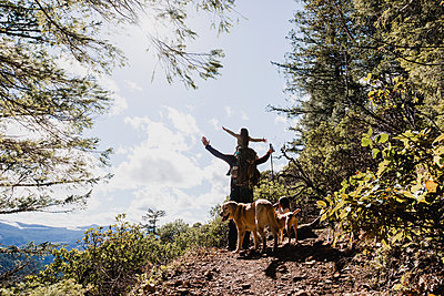 Male hiker carrying daughter while standing by dogs on mountain against sky - p1166m1474550 by Cavan Images