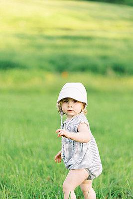 Little girl exploring a meadow. - p1166m2153874 by Cavan Images