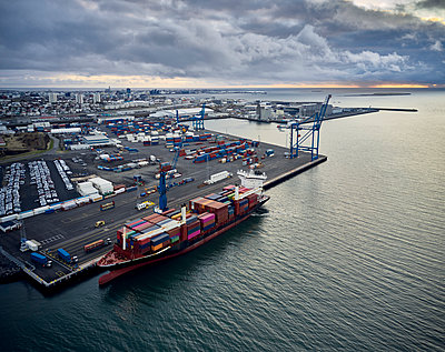Cargo ship with containers in industrial port - p1166m2261883 by Cavan Images