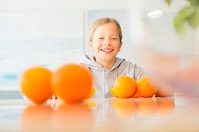 Portrait of happy girl with oranges in kitchen - p300m1580925 von Nell Killius