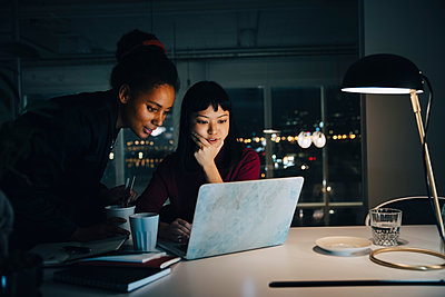 Confident businesswomen planning strategy while using laptop in night meeting at office - p426m2194827 by Maskot