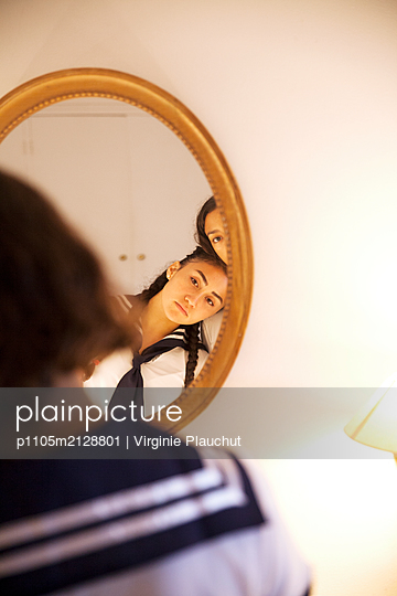 Two girls in front of a mirror - p1105m2128801 by Virginie Plauchut