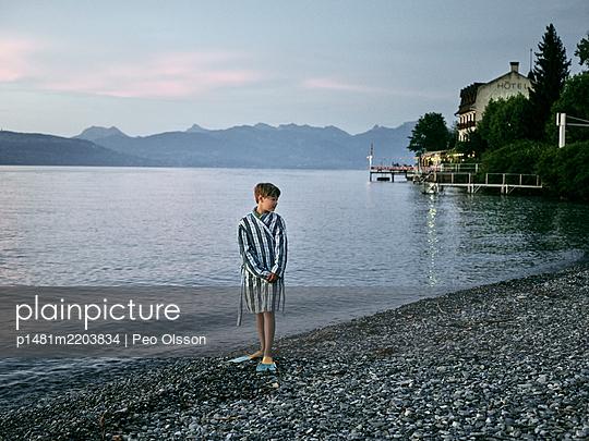 Boy in a bathrobe on pebble beach, Lake Geneva, Frankreich - p1481m2203834 by Peo Olsson