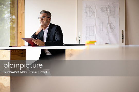 Thoughtful businessman using digital tablet while sitting at home - p300m2241486 by Peter Scholl