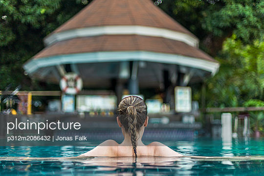 Young woman relaxing in swimming pool - p312m2086432 by Jonas Falk