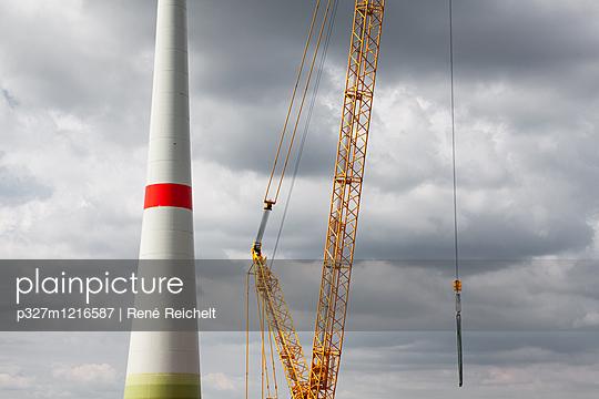 Windrad mit Kran vor dunklen Wolken - p327m1216587 von René Reichelt