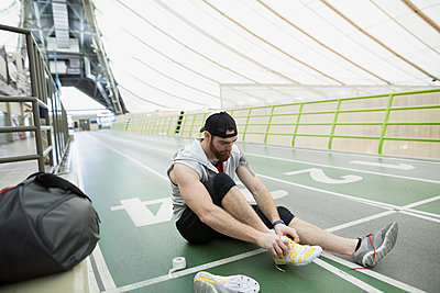 Runner tying shoelace at indoor track - p1192m1129684f by Hero Images