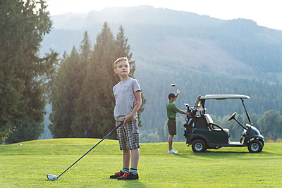 Thoughtful boy standing with golf club in the course - p1315m1565186 by Wavebreak