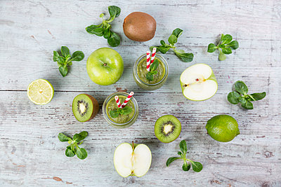 Two glasses of green smoothie and ingredients on wood - p300m1228469 by JLPfeifer