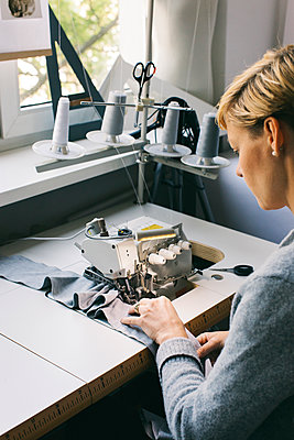 Woman using sewing machine on table in studio - p300m2029801 by Visualspectrum