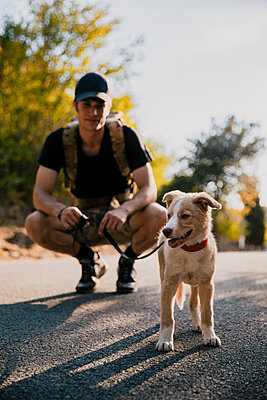 Male hiker looking at dog while crouching on footpath - p300m2287120 by Aitor Carrera Porté