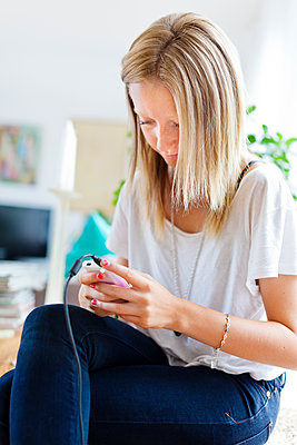 Woman using smartphone at home - p312m1551950 by Johner Images
