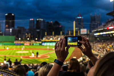 Hands of woman photographing baseball game with cell phone - p555m1504048 by Steve Prezant