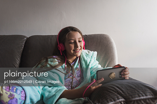 Cute little girl watching videos on the smarthpone - p1166m2212549 by Cavan Images