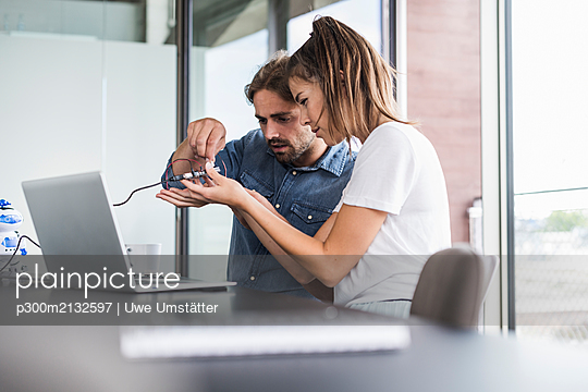 Young woman and man working on computer equipment in office - p300m2132597 by Uwe Umstätter