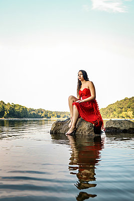 Woman in red dress on a rock - p1019m2111183 by Stephen Carroll