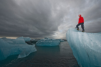 woman climbing iceberg on the south coast of Iceland using ice pick - p1166m2269500 by Cavan Images