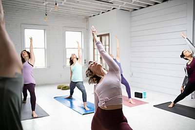 Women practicing yoga reverse warrior pose in yoga class - p1192m1583331 by Hero Images