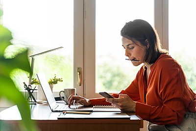 Businesswoman using mobile phone while working at home - p300m2206513 by VITTA GALLERY