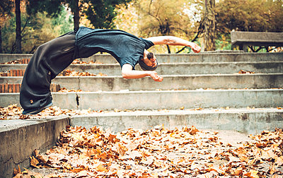 Young man jumping over autumn leaves in public park - p300m2206677 by klublu