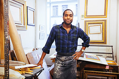 Portrait of smiling young male artist standing with hand on hip at framing workshop - p426m2089101 by Maskot