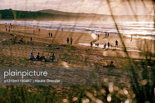 Sonnenbadende bei Sonnenuntergang am Strand, Playa de Valdearenas, westlich Santander, Kantabrien, Spanien - p1316m1160487 von Hauke Dressler