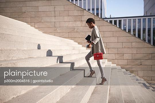 Businesswoman walking up stairs - p300m2004516 von gpointstudio