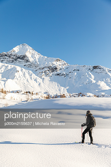 Woman walking with snowshoes in fresh snow in the mountains, Valmalenco, Italy - p300m2155637 by Michela Ravasio