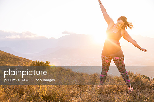 Plus-Size-Model doing sports in the countryside at sunset - p300m2167478 by Floco Images