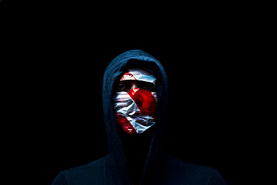 hooded man in the shadow and wrapped in crime scene tape red and white  - p1165m952598 by Pierro Luca