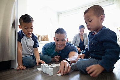 Family playing with dominos on floor - p1192m2088615 by Hero Images