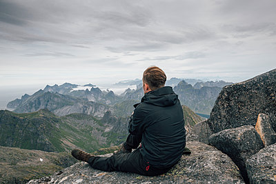 Norway, Lofoten, Moskenesoy, Young man sitting at Hermannsdalstinden, looking over Kjerkefjord - p300m2004183 von Gustafsson