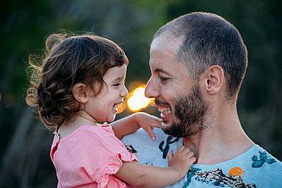 Happy father holding his daughter outdoors at sunset - p300m2058820 von Gemma Ferrando