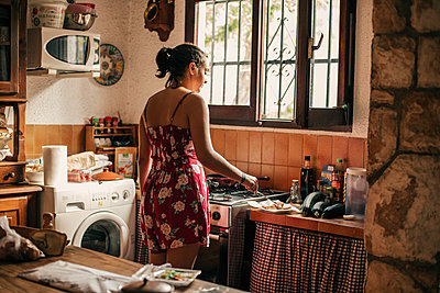 Rear view of woman cooking in kitchen - p300m2131663 von Aitor Carrera Porté