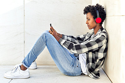 Young Afro woman using mobile phone while sitting against retaining wall - p300m2241327 by Veam