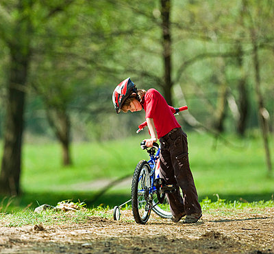 Boy climbing on bicycle in park - p429m800993f by WALTER ZERLA