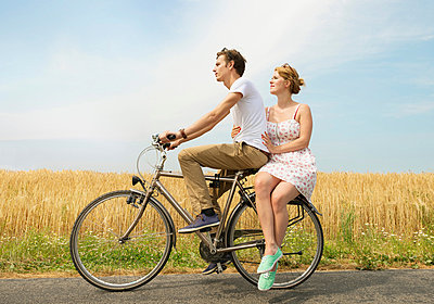 Couple riding bicycle - p429m839083 by Mischa Keijser
