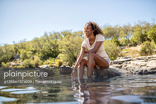 Junge Frau badet ihre Füße im Fluss - p1355m1574209 von Tomasrodriguez