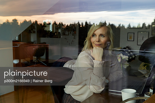 Portrait of blond woman with laptop behind windowpane at home - p300m2166949 by Rainer Berg