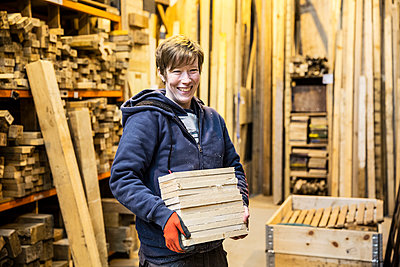 Smiling blond woman wearing work gloves standing in a workshop, holding stack of wood, looking at camera. - p1100m1575746 by Mint Images