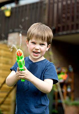 Little boy playing with a water pistol - p1221m1158623 by Frank Lothar Lange