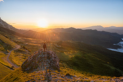 Italy, Umbria, Sibillini National Park, hiker standing on viewpoint at sunrise - p300m2059208 by Lorenzo Mattei