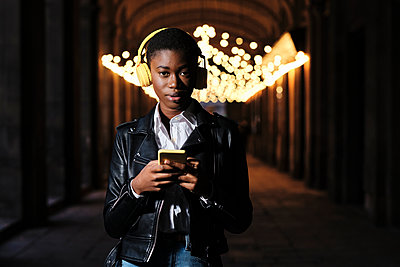 Young woman with headphones and mobile phone staring while standing at corridor - p300m2250238 by Alvaro Gonzalez