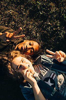 High angle portrait of smiling friends gesturing peace sign while lying on field during sunny day - p426m2075164 by Maskot