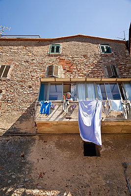 Woman hanging laundry on cloth line - p528m713691 by Kari Kohvakka