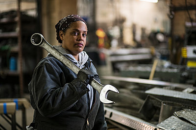 African American worker holding wrench in factory - p555m1311984 by Jetta Productions