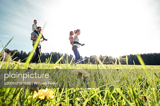 Happy family with two kids on a meadow in spring - p300m2167632 by Wilfried Feder
