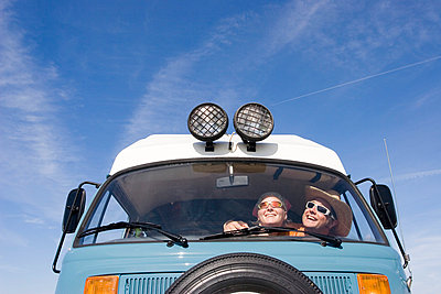 Low angle view of a couple inside a camping van against blue sky leisure lifestyle light lights love - p1025m788575f by Nicklas Blom